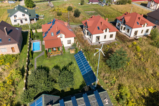 Aerial view of a new autonomous house with solar panels, water heating radiators on the roof, wind powered turbine and green yard with blue swimming pool.