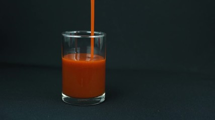 Fototapete - Pour tomato juice into a glass on black background, put a white straw and take it away.