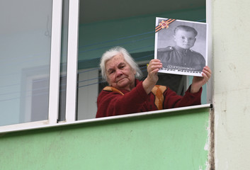 A woman holds a picture of a World War Two soldier as she watches a concert performed for veterans by a regional military band ahead of the Victory Day celebrations in Rostov-on-Don