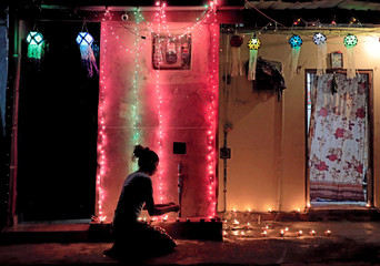 A girl lights oil lamps in front of her house decorated with lights and lanterns, on the following day of Vesak day, in Colombo