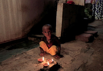A boy looks on next to his lit oil lamps in front of his house on the following day of Vesak day, in Colombo