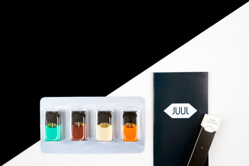 Juul vapor on juul logo booklet laying flatlay on table next to flavoured juul pods in package. White and black background. Nicotine and cigarettes concept.