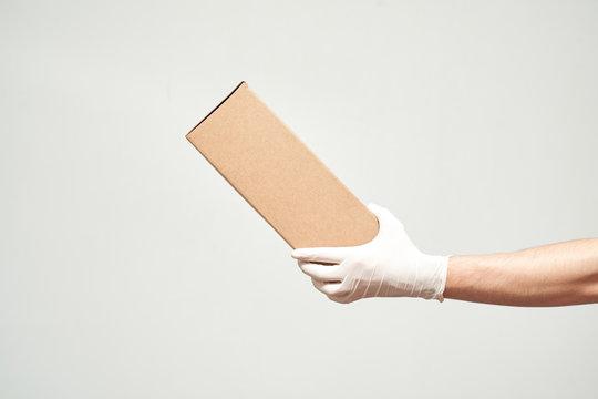 Hand in latex gloves holding cardboard box