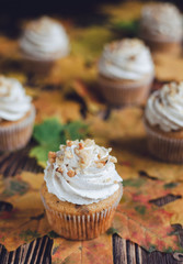 Homemade orange yellow cupcakes with walnuts, on the wooden rustic background, decorated with fall leaves. Selective focus,