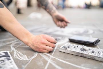Street art, pavement artist drawing on pavement and using smartphone
