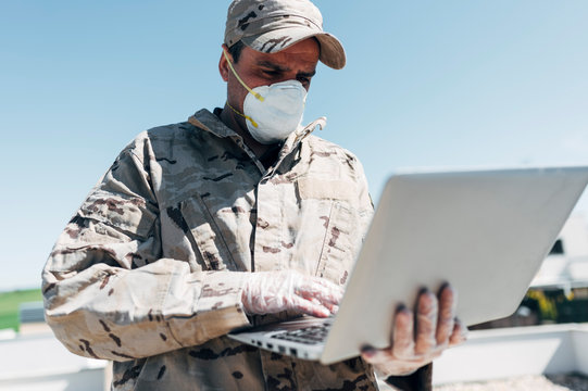 Soldier with face mask on emergency operation, using laptop