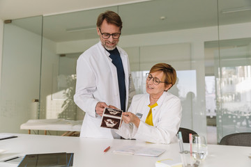 Two doctors discussing ultrasound images of fetus