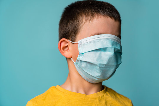 Portrait of boy covering his face with mask