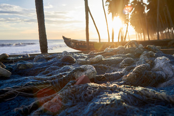 Ghana, Keta, Fishing nets lying in front of boats left on coastal beach at sunset