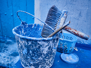 Morocco, Chefchaouen Province, Chefchaouen, Paintbrush and metal bucket covered in blue paint