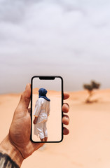 Hand holding smartphone with foto of man walking in the desert