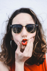 Portrait of young woman with red lips wearing sunglasses pouting mouth