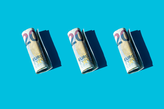 Twenty euro rolled banknotes on a blue background