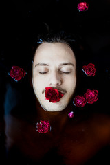 Portrait of young man with red rose in his mouth floating in water