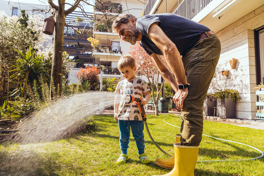 Father and son watering the lawn in garden