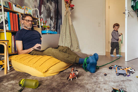 Son tying his father working on laptop in children's room