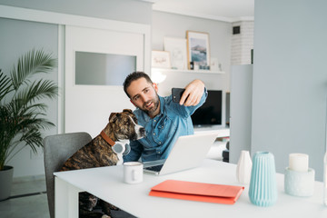 Mid adult man taking selfie with dog while working from home during coronavirus crisis, Almeria, Spain, Europe