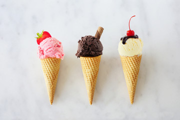 Ice cream cone assortment. Strawberry, chocolate and vanilla in waffle cones. Top view over a white marble background.