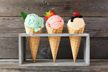 Ice creme cone assortment in waffle cones against a wood background. Mint, strawberry and vanilla flavors with toppings.
