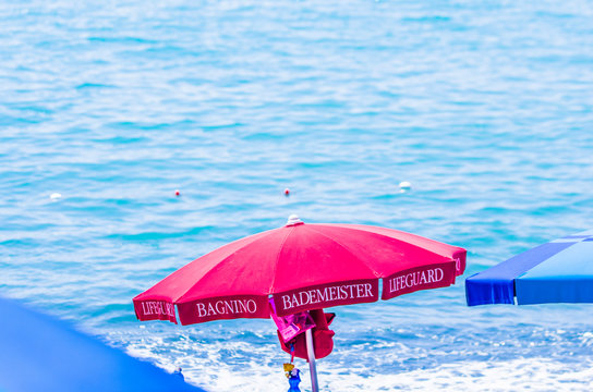 red umbrella and lifeguard chairs for your safety at the sea