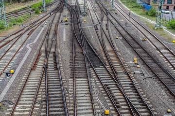 Multiple railroad tracks with junctions at a railway station in a perspective view