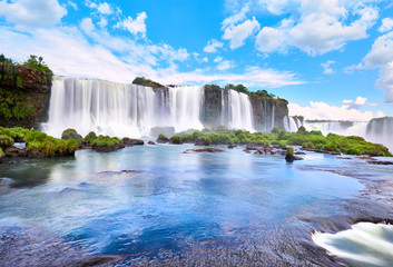 Iguazu waterfalls in Argentina, view from Devil's Mouth. Panoramic view of many majestic powerful water cascades with mist. Panoramic image with reflection of blue sky with clouds. Wall mural