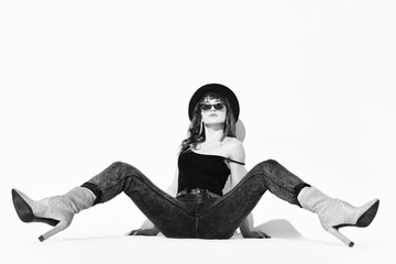 Young beautiful brunette woman in stylish casual clothing, hat and high heels boots sitting on floor with legs stretched out