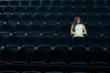 Amazing shot of a beautiful young female sitting in a cinema hall Fotomurales