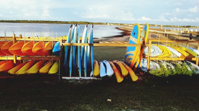 Multi Colored Surfboards And Paddleboards Lined Up On Beach