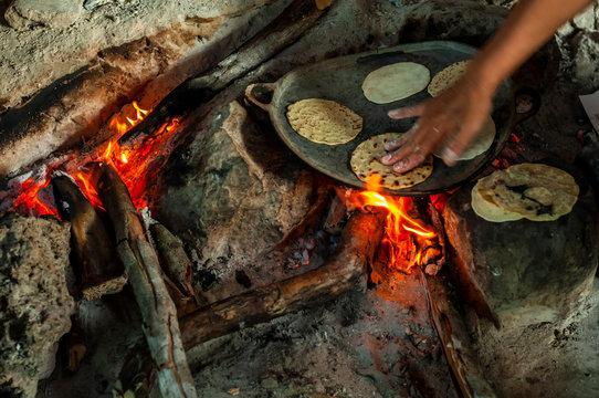 Preparación de tortillas caseras en fogón tradicional de vivienda en Yucatán, México.