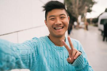Asian man taking a selfie.