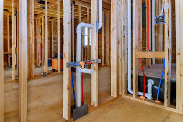 Applying pipe drain plumbing with hot red and cold blue pex pipe inside a house frame