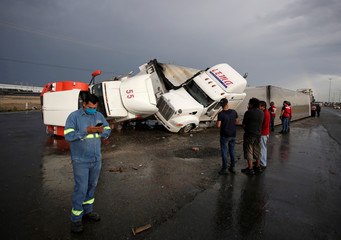 People stand near damaged trucks after a tornado hit the municipality of Apocada