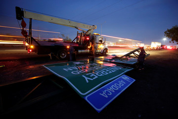 Workers attempt to raise road signs after a tornado hit the municipality of Apocada