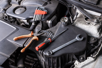 A set of metal spanners, screwdrivers, Pliers and ratchet  of different sizes lies under the hood of the car on an oil cooler. Concept of car repair and tools in car service