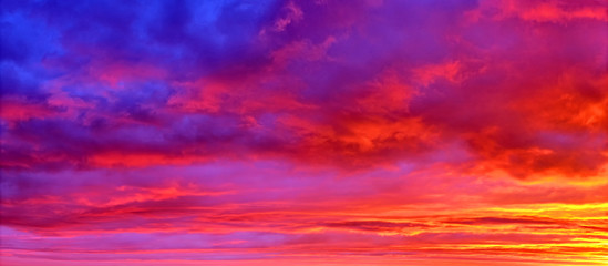mellow sunset sky landscape background natural color of evening cloudscape panorama with sun below horizon ultra wide panoramic view Red orange and blue colors of evening nature