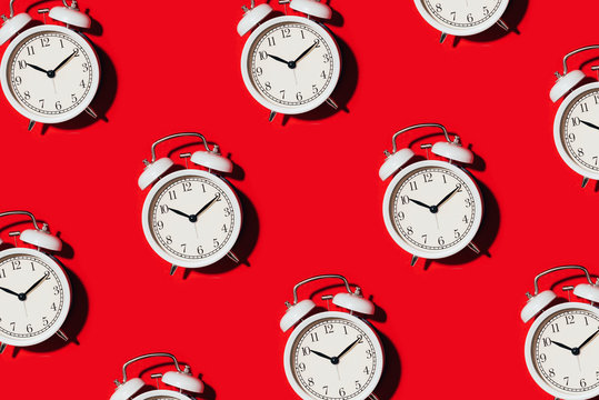 Pattern of white alarm clock on red background. Wake up alert concept. Morning routine. Back to school concept. Minimalist style design. Packing design. Creative design, minimal flat lay concept