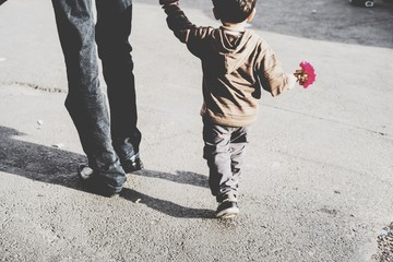 Rear View Of Man Walking With Son On Street