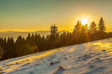 Foto auf Gartenposter Olivgrun Snow Covered Landscape Against Sky During Sunset
