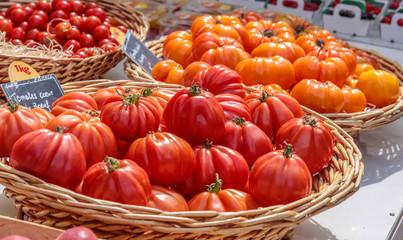 Saftige rote und orange Tomaten an einem Marktstand in Gordes