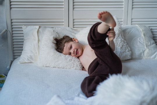 sleep in bed, play on the bed, the boy is resting during self-isolation, home and comfort