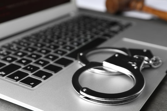 Laptop and handcuffs on table, closeup. Cyber crime