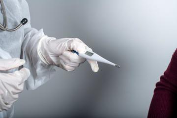 medico con maschera, occhiali e tuta di protezione misura la temperatura a un paziente