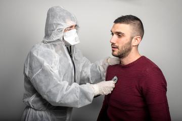operatore sanitario con maschera e tuta di protezione con stetoscopio e termometro
