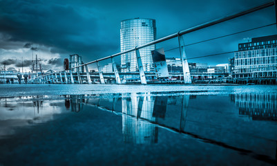 Belfast architecture along River Lagan reflected in a puddle.