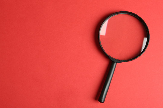 Top view of magnifying glass on red background, space for text. Search concept