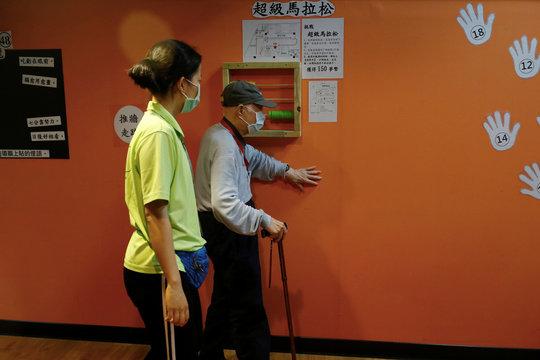 Senior walks along a wall at an elderly day care center in Taipei