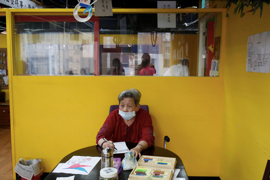 Senior works on a math exercise at an elderly day care center in Taipei