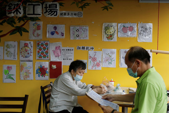 Senior does math exercise at elderly day care center in Taipei