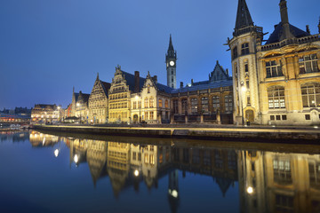 Illuminated promenade near St Michael bridge and St Bavo's Cathedral in a historical center of Ghent city. Night cityscape. Symmetry reflections on the water. Travel guide, sightseeing theme. Belgium Fototapete